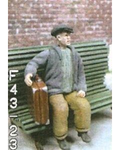 Mann, sitzend mit Koffer