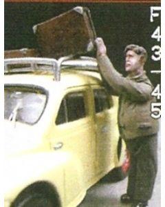 Mann, Koffer auf Autodach ladend